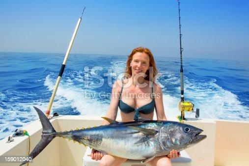 156872766 istock photo Woman in blue bikini on a boat holding huge bluefin tuna 159012040