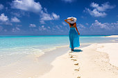 Attractive traveler woman in blue dress walks on a tropical beach and enjoys her summer vacation