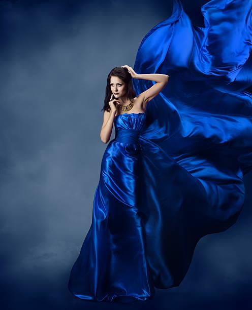 frau im blauen kleid mit fliegenden seide stoff - abendkleid lang blau stock-fotos und bilder