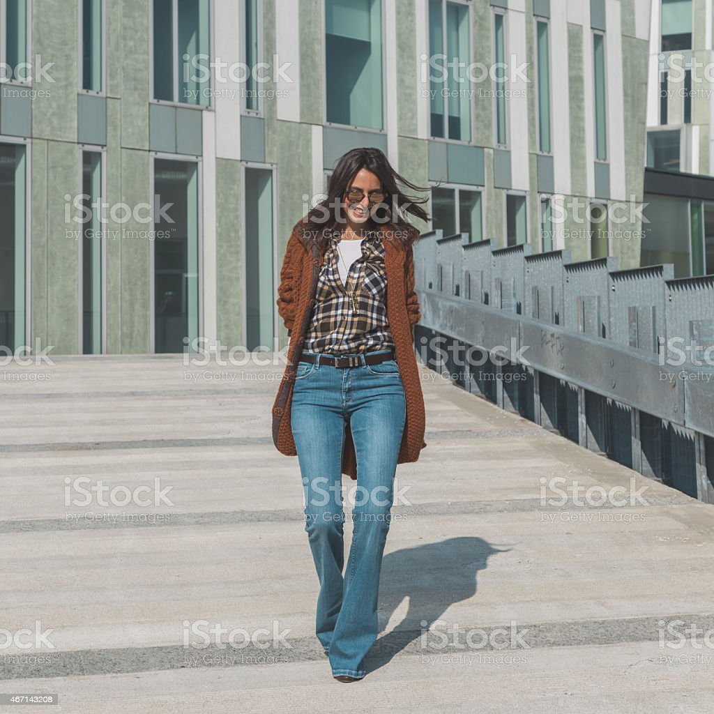 A woman in blue jeans leaving a business building stock photo