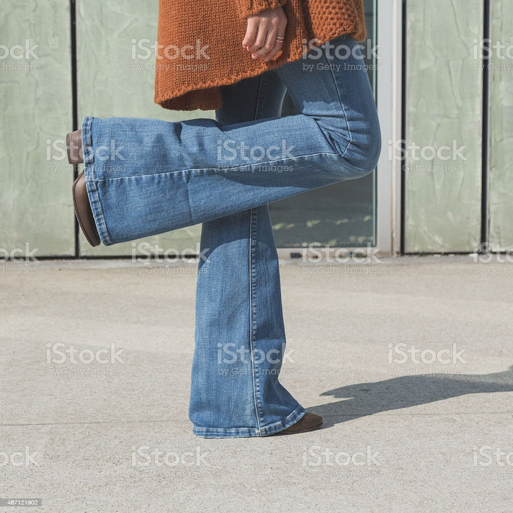 Woman in blue jeans standing on one foot on cement floor stock photo