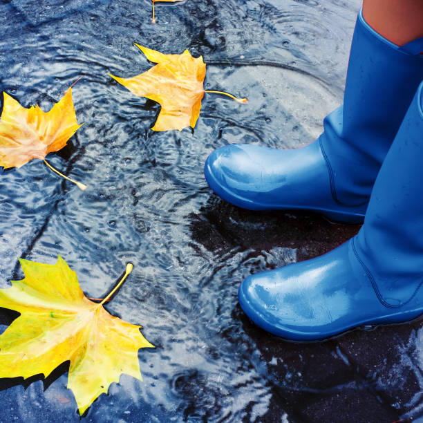 Woman in blue rain boots standing in puddle stock photo