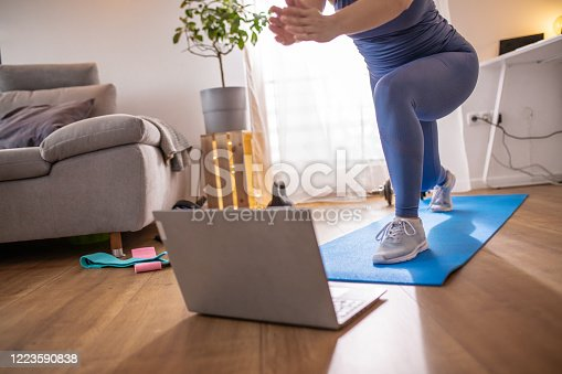 Low section shot of a woman in blue sportswear exercising on an exercise mat and using laptop at home