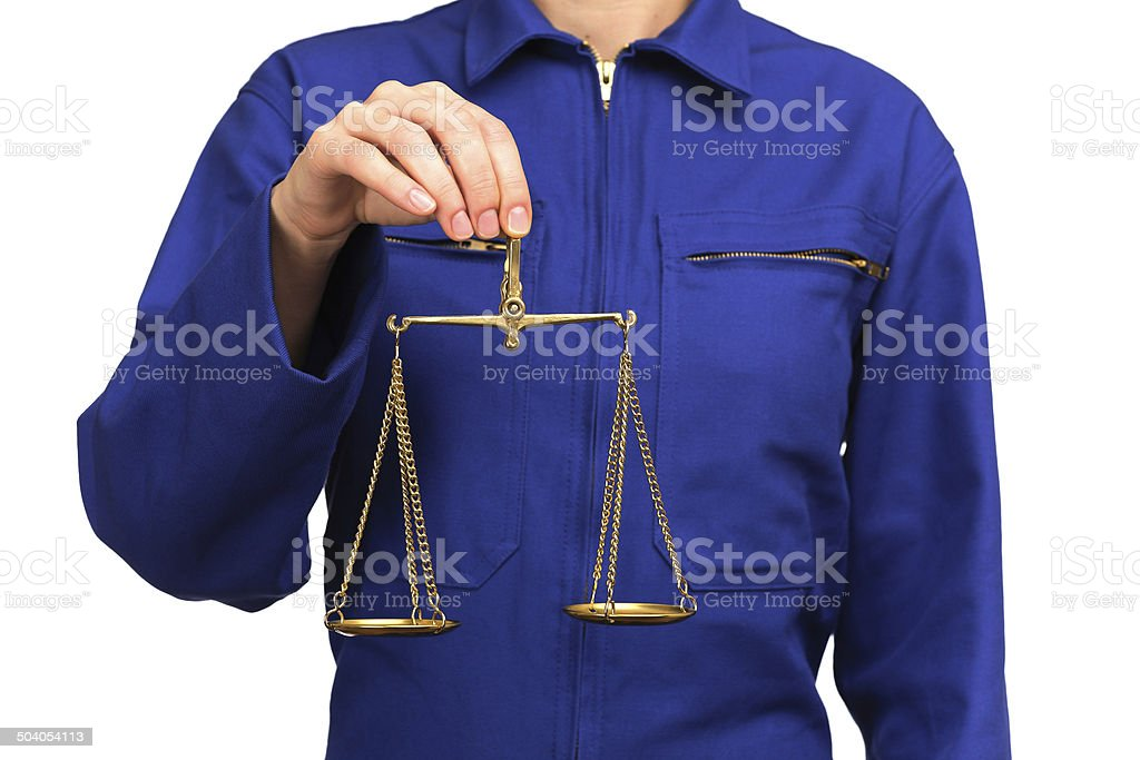 woman in blue work uniform holding a scale of justice stock photo