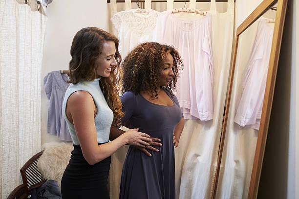 woman in boutique changing room with friend trying on dress - einen gefallen tun stock-fotos und bilder