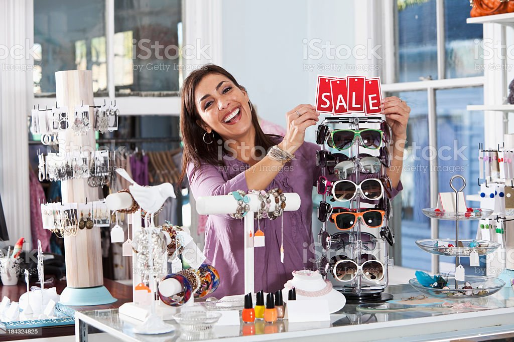 Woman in boutique with a sale sign royalty-free stock photo
