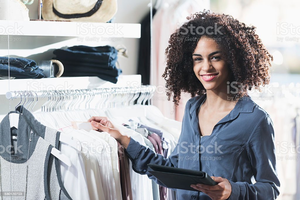 Woman in boutique with digital tablet stock photo