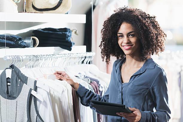 woman in boutique with digital tablet - verkoopster stockfoto's en -beelden