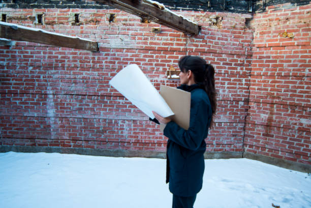 Woman in brick building planning renovations with papers in hand stock photo