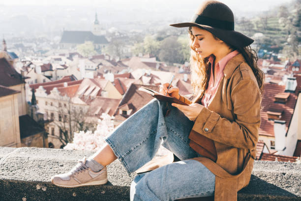Woman in brown hat writing in the diary in view point stock photo