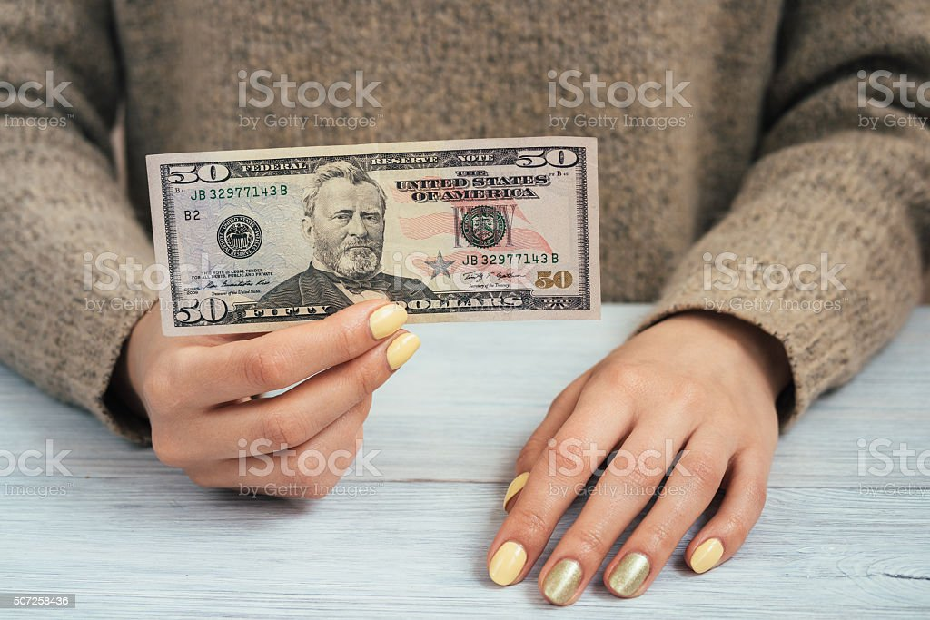 Woman in brown sweater with yellow manicure holding a banknote stock photo