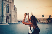 Tourist in Budapest sightseeing and taking photos with smartphone