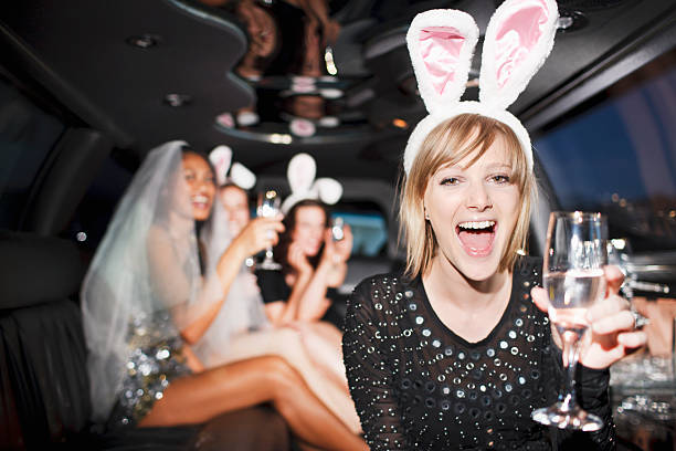 Woman in bunny ears drinking champagne in limo stock photo