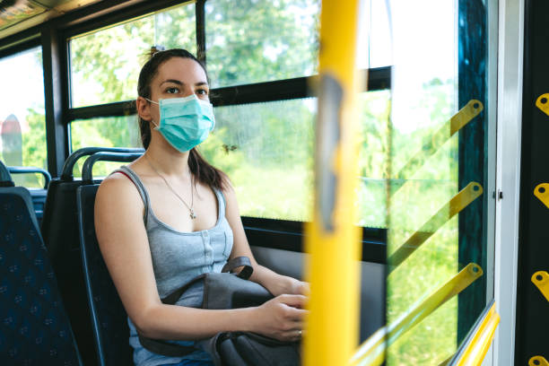 Woman in bus wearing face mask stock photo