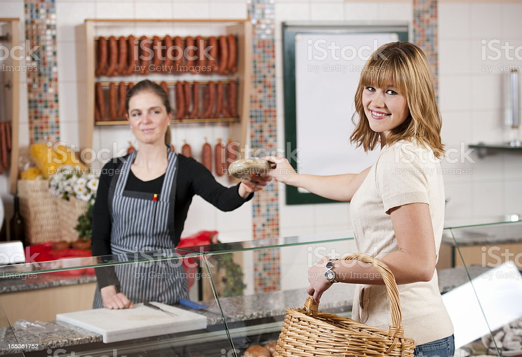Woman in butchers shop stock photo