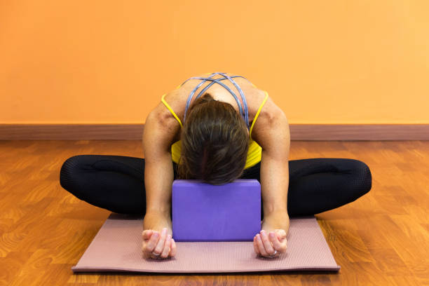 Woman in butterfly yin yoga asana with forehead resting on purple prop stock photo