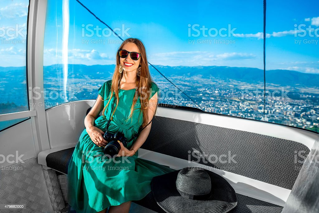 Woman in cable car with cityscape view stock photo
