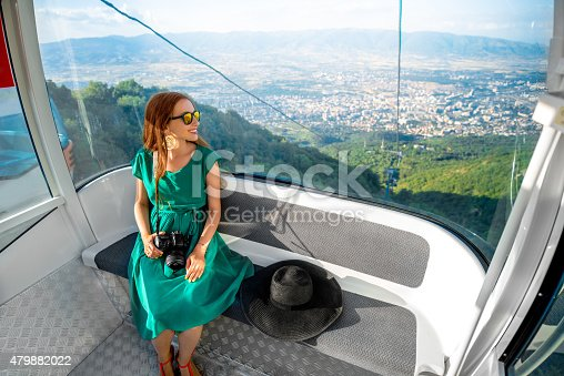 Young woman tourist sitting in cable car on the way to the top of Vodno mountain near Skopje city in Macedonia