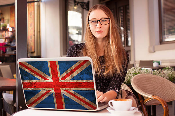Woman in  cafe notebook with flag of Britain stock photo