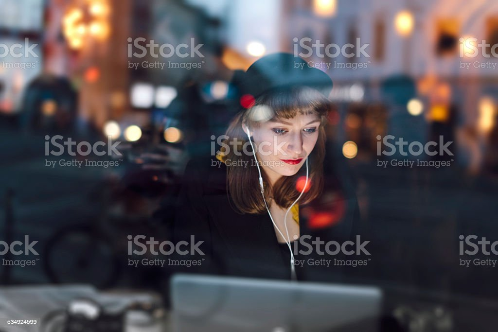 Woman in Cafe Working on Laptop stock photo