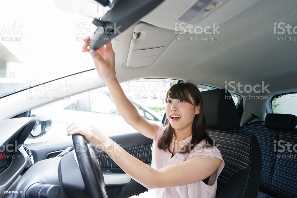 Woman in car checking mirror royalty-free stock photo