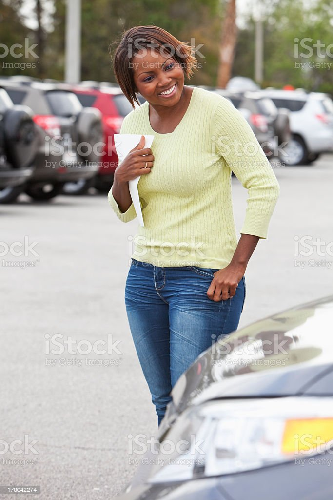 Woman in car lot holding brochure royalty-free stock photo