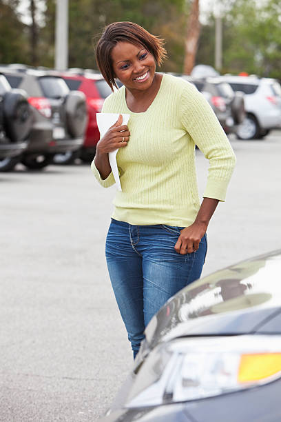 Woman in car lot holding brochure stock photo