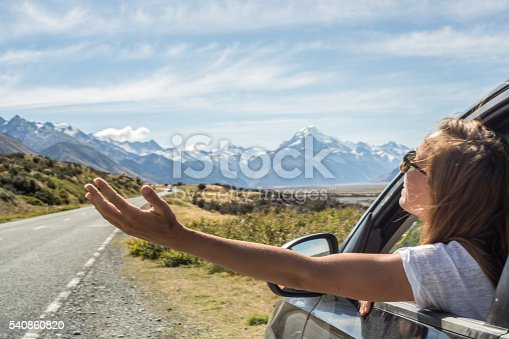 istock Woman in car on roadside stretches arms out of window 540860820