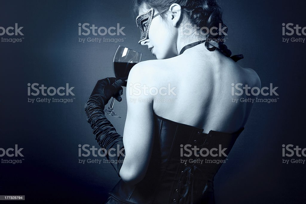 woman in carnival mask and a glass of red wine. royalty-free stock photo