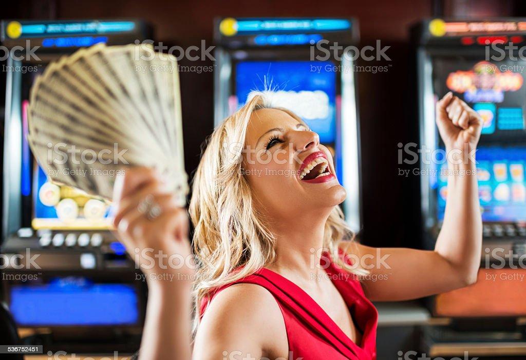 Woman in casino winning at slot machine. stock photo