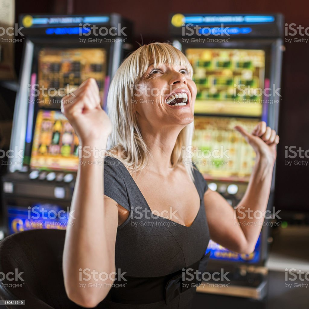 Woman in casino winning on slot machine. stock photo