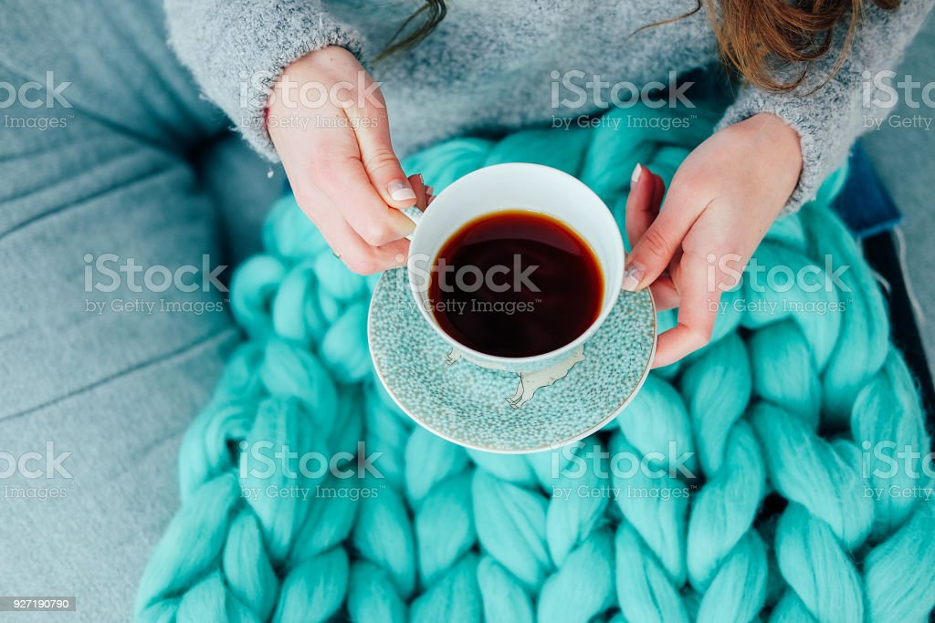 Woman in casual clothes sitting in the living room and drinking tea stock photo