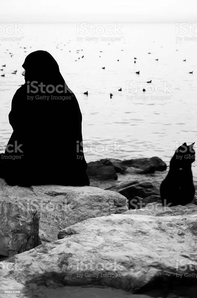 Woman in Chador and Black Cat royalty-free stock photo