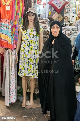 Tehran, Iran - April 29, 2017:  A Muslim woman in a black Islamic chador stands near a full-length female mannequin dressed in a short summer dress, sleeveless, with a yellow floral pattern.