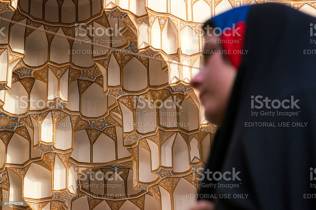 Woman in chador passing in front of decorative ornamented vaulting stock photo