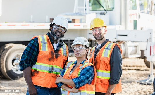 Multi-ethnic construction workers with a female foreman at a job site. The mid adult woman, in her 30s, is standing with male coworkers with her arms crossed.