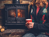 A young woman wearing a christmas jumper is sitting by the fire with a mug in her hand