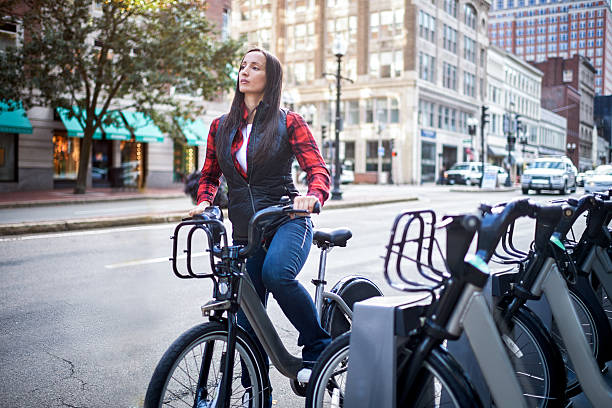 Woman in city riding a bicycle stock photo