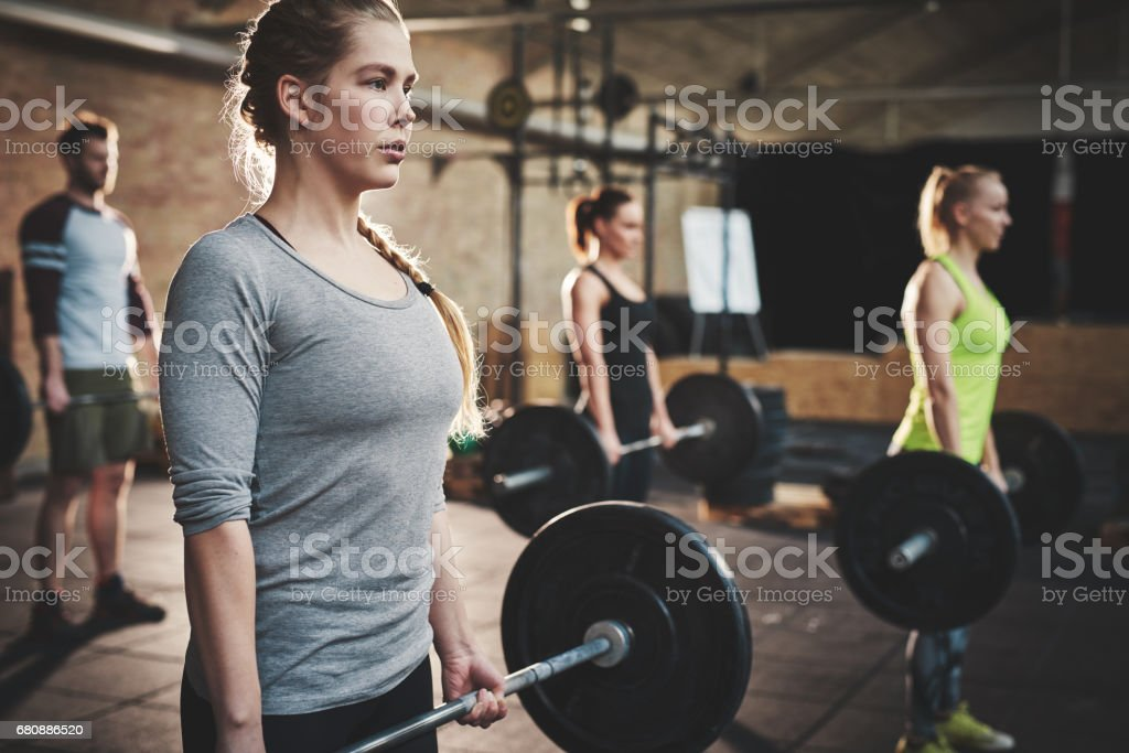 Woman in class doing dead lift barbell exercise royalty-free stock photo