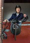 middle-aged woman standing at stable door, holding whip, hands leaning on classic English saddle. Cap on, looking at camera.