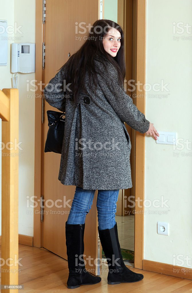 Woman in coat leaving the house stock photo