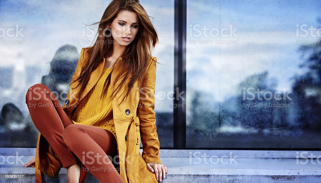 Woman in coat sitting against city landscape royalty-free stock photo