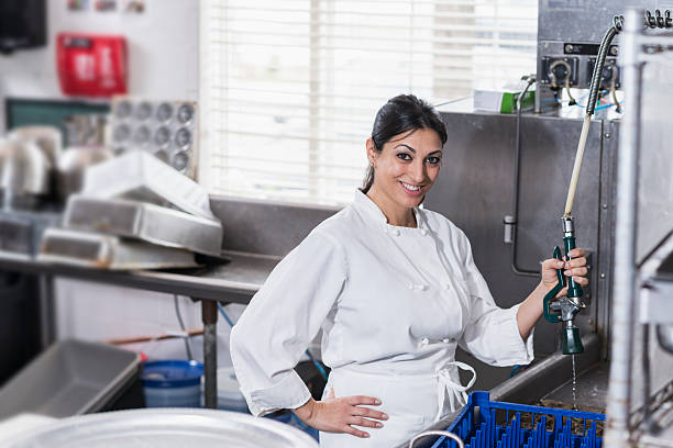 woman in commercial kitchen at sink cleaning dishes - commercial dishwasher stock photos and pictures