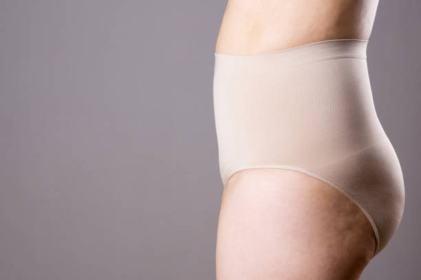 Woman in corrective panties, overweight female body in shapewear on gray background stock photo