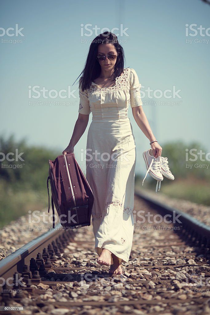 Woman in cotton beige dress barefoot on the railway Woman in romantic beige cotton old fashioned dress with retro suitcase walking on the railway  waiting for a train Adult Stock Photo