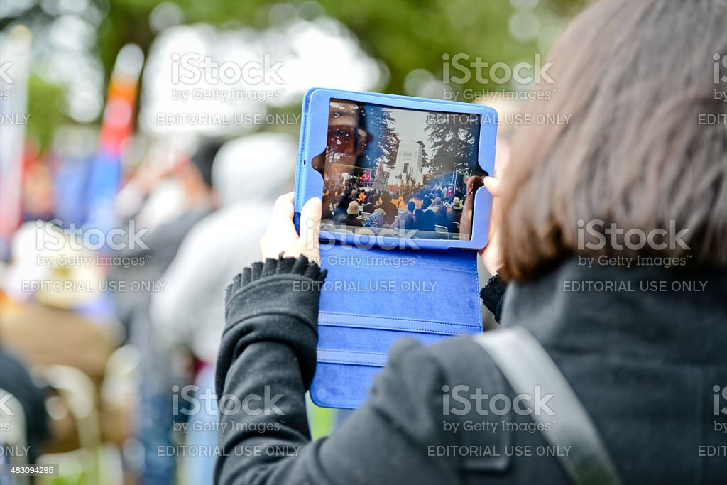 Woman in crowd filming US Memorial Day Ceremony with iPad royalty-free stock photo
