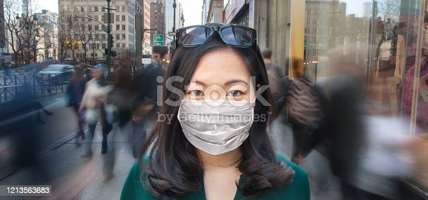 Young Asian woman wearing a surgical mask as crowd of people walk past her in blur motion.