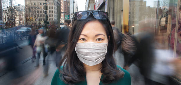 Woman in crowd wearing surgical mask Young Asian woman wearing a surgical mask as crowd of people walk past her in blur motion. east asian ethnicity stock pictures, royalty-free photos & images