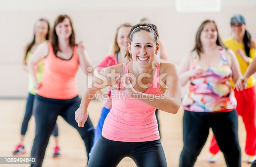 A group of women in bright athletic wear working out in a dance exercise class