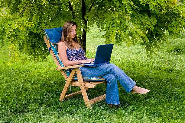 Woman in deck chair with laptop under tree canopy stock photo